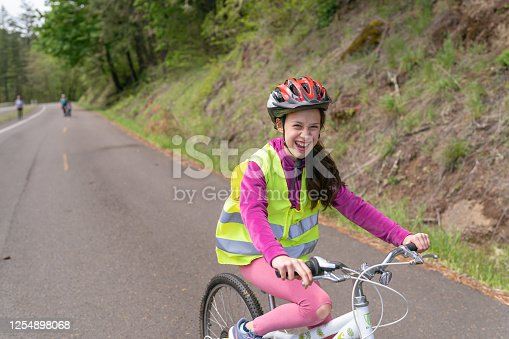 A 12-year old wearing a yellow safety vest and helmet rides her bicycle along a rural road in the forest. She is riding toward the camera and there are several people walking in the background.