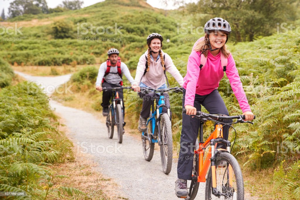 Pre-teen girl riding mountain bike with her parents during a family camping trip, close up - Royalty-free 12-13 Anos Foto de stock