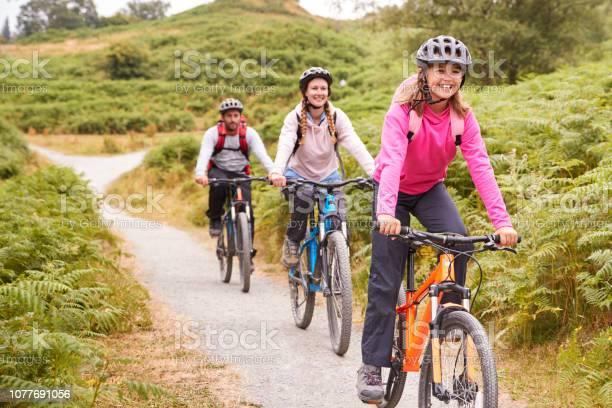 Preteen Girl Riding Mountain Bike With Her Parents During A Family Camping Trip Close Up - Fotografias de stock e mais imagens de 12-13 Anos