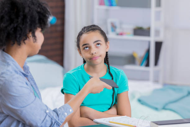 Preteen girl rolls eyes as mom takes away her phone Mixed race preteen girl rolls her eyes as her mom takes away her smart phone. rolling eyes stock pictures, royalty-free photos & images