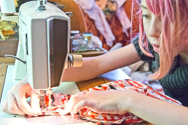 Pre-teen girl sewing with a machine stock photo