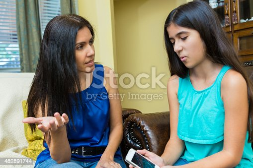 istock Preteen girl showing broken cell phone to her frustrated mom 482891744