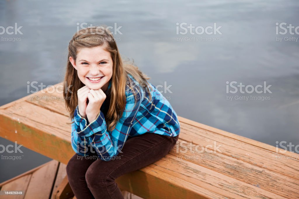 Preteen girl sitting by water royalty-free stock photo
