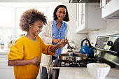 Pre-teen girl standing at hob in the kitchen using spatula and frying pan, preparing food with her mother, side view