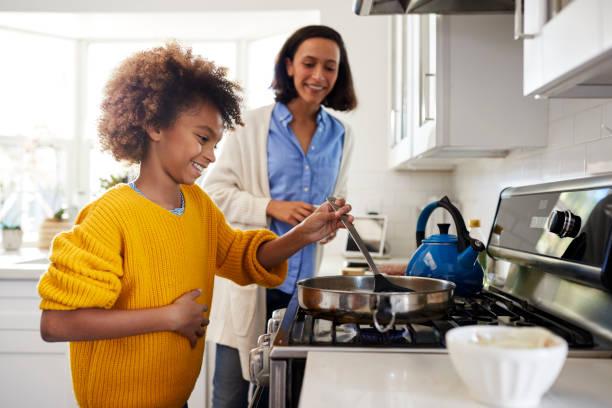 ragazza pre-adolescente in piedi al piano cottura in cucina usando spatola e padella, preparando il cibo con sua madre, vista laterale - cucinare foto e immagini stock