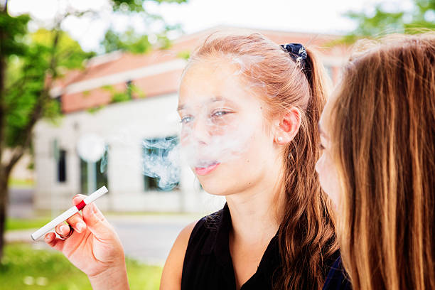 Preteen girl tries e-cigarette with her friend Preteen girl tries e-cigarette under the influence of her friend. electronic cigarette stock pictures, royalty-free photos & images
