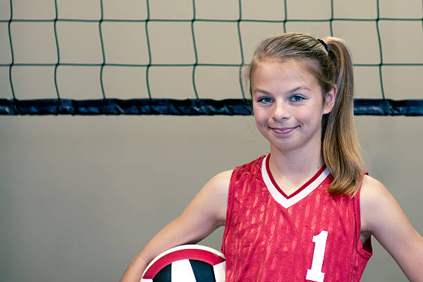 Preteen girl volleyball player with net in background stock photo