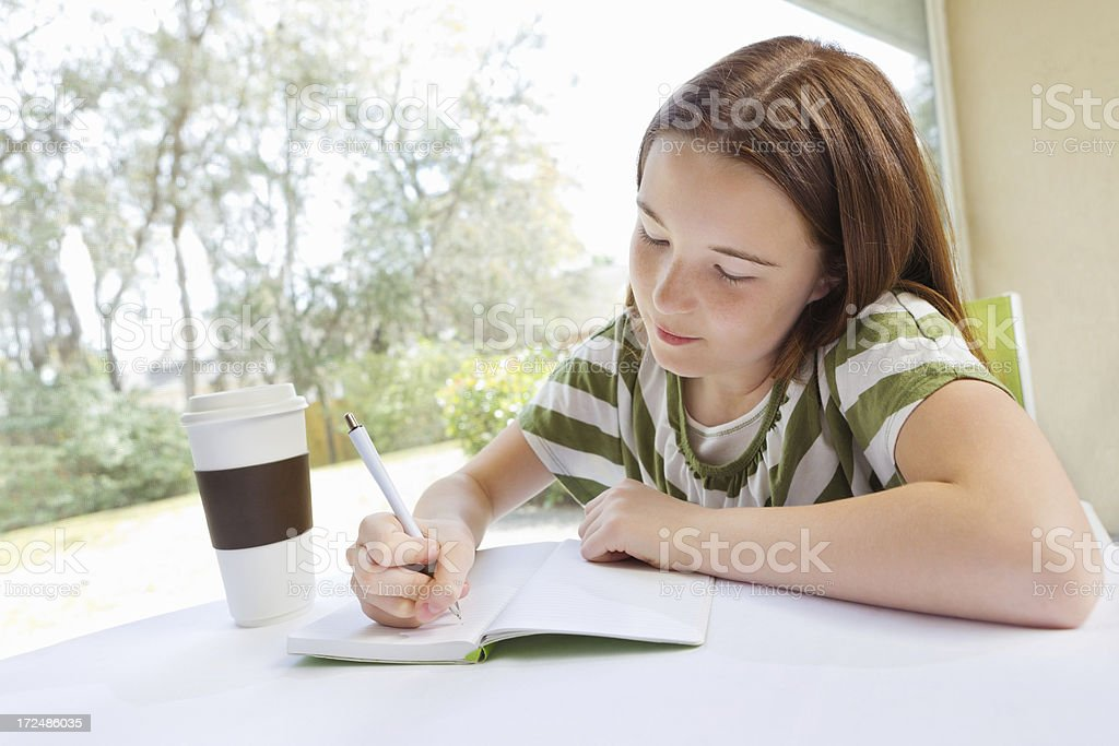 Preteen girl writing in journal and drinking coffee royalty-free stock photo