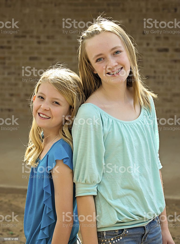 Pre-teen girls back-to-back royalty-free stock photo