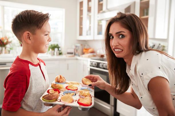 pre-hispanischen teenboy präsentieren die kuchen, die er gebacken hat seine enttäuschten mutter, nahaufnahme - super torte stock-fotos und bilder
