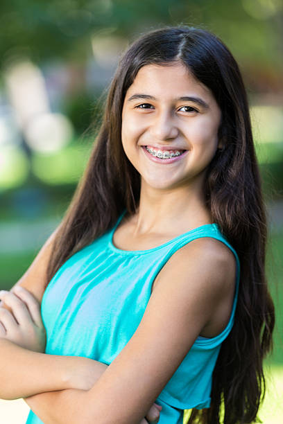 Preteen Hispanic girl with braces smiling outdoors stock photo