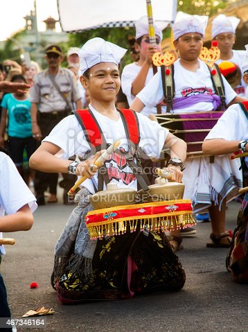 Lovina, Indonesia - March 20, 2015: Pre-teen Indonesian boy playing Bonang metallophones during  Ngrupuk parade in Lovina, Bali, Indonesia. The kid is kneeling down and plays proudly with a big, confident smile while the crowd watches. Some of his musical bandmates are visible in the background.