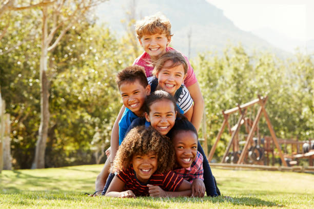 pre-teen school friends lying a pile in a park - children only stock pictures, royalty-free photos & images