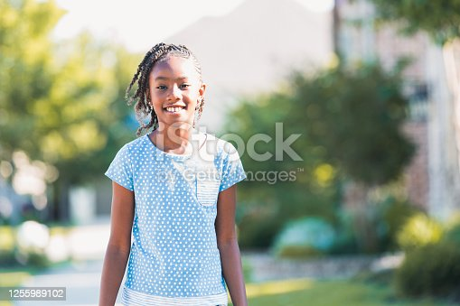 Young preadolescent girl stops to pose for a photo on her morning walk.