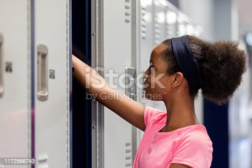 Preteen girl takes something out of her locker after PE class.