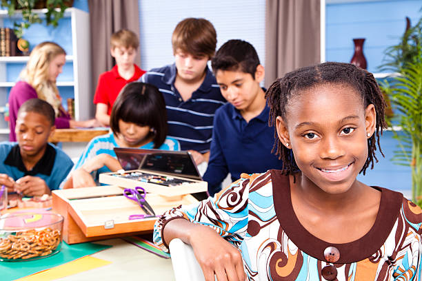 Pre-teen students at home working on school project stock photo