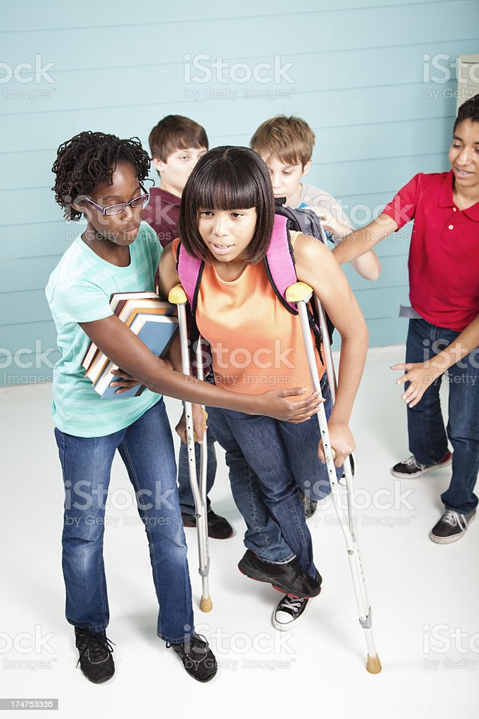 Pre-Teen tripping classmate on crutches stock photo