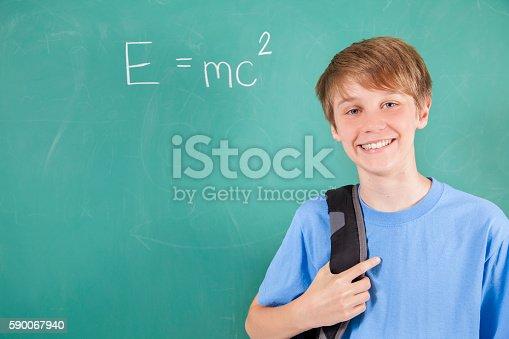 istock Pre-teenage student with math equation on school chalkboard. 590067940