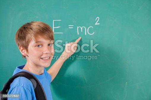 istock Pre-teenage student with math equation on school chalkboard. 590072832