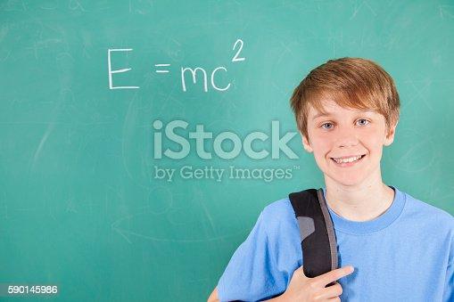 istock Pre-teenage student with math equation on school chalkboard. 590145986
