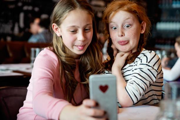 Preteens Mädchen machen Selfies an einem Restauranttisch. – Foto