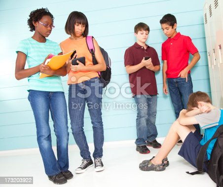 Pre-teens at school making fun of boy sitting on floor by the lockers.   MORE LIKE THIS...in lightboxes below.
