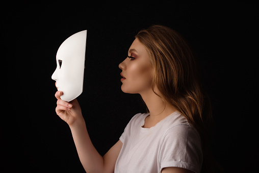 Profile view of blond woman holding white mask acting out and pretending, feeling depressed