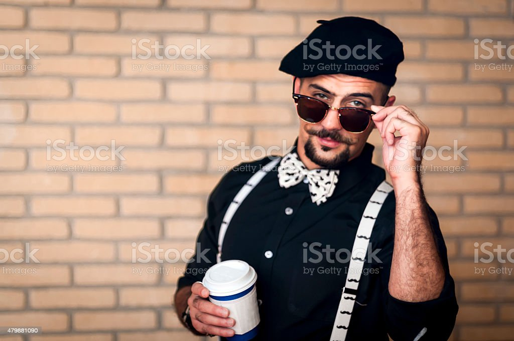Pretentoius hipster giving a over the glasses look to the camera stock photo