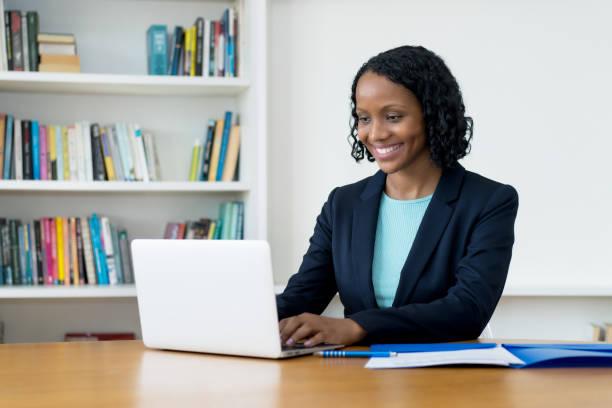ziemlich afrikanische amerikanische geschäftsfrau arbeitet am computer - geschäftskleidung stock-fotos und bilder