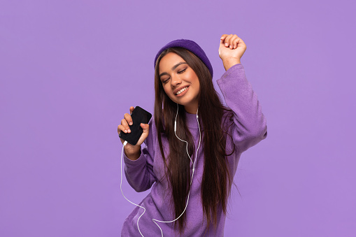 Pretty african-american girl in a hat and sweater listening to music on a mobile phone with wired headphones and dancing isolated over purple background. Enjoying life.