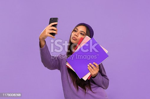 istock Pretty african-american teenager student in a hat and sweater holding folders and making selfie with a smartphone standing isolated over purple background. Concept of education 1179008268