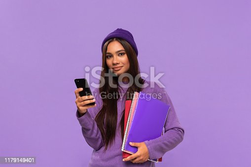 istock Pretty african-american teenager student in a hat and sweater holding folders and looking surprised checking notification on a smartphone standing isolated over purple background. Concept of education 1179149401