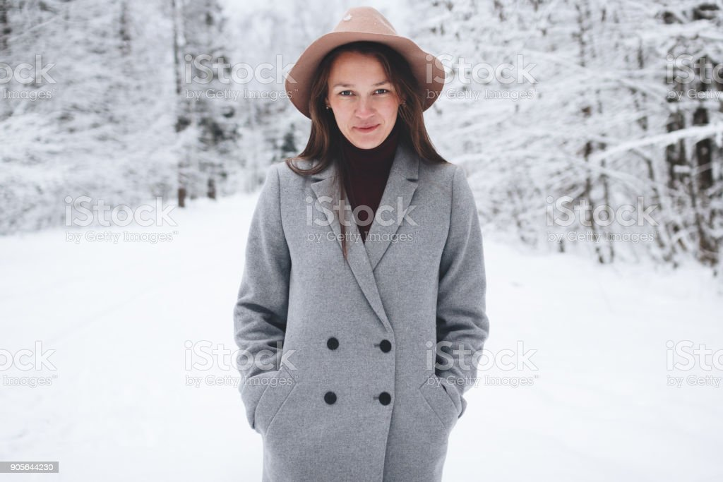 7758b4fcd78 Pretty And Cute Young Woman In Coat And Hat Walking In Winter Forest ...