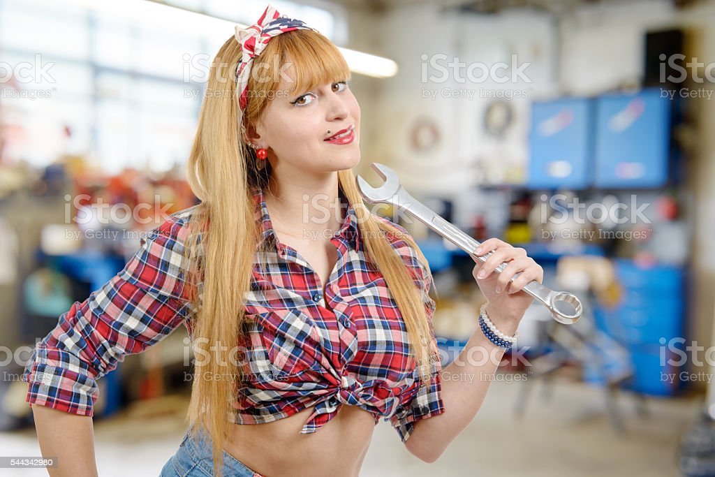 a pretty and sexy woman mechanic in garage