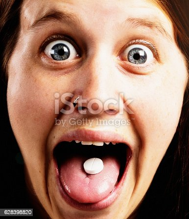 istock Pretty and very excited girl showing pill on her tongue 628398820