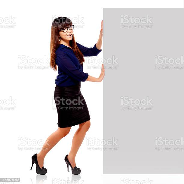 Pretty asian brunette businesswoman in happy face showing an empty blankboard isolated on white background