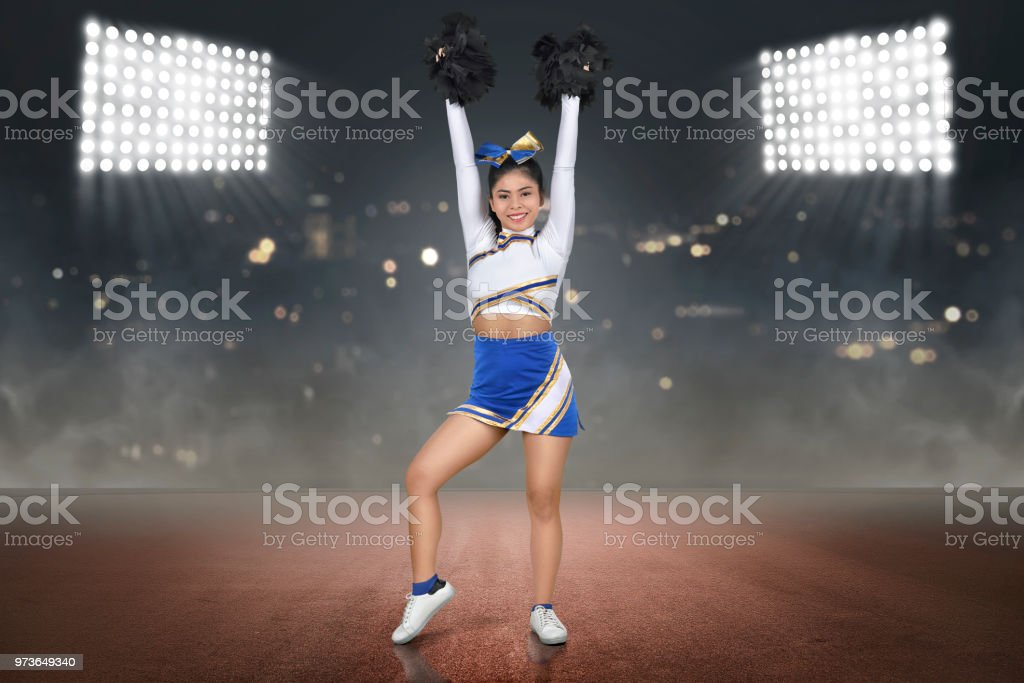 Pretty asian cheerleader with hands holding pom-poms in the air stock photo
