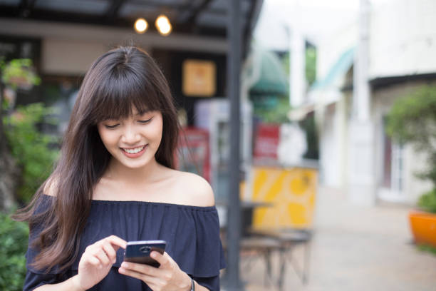 pretty asian girl happy with smart phone stock photo