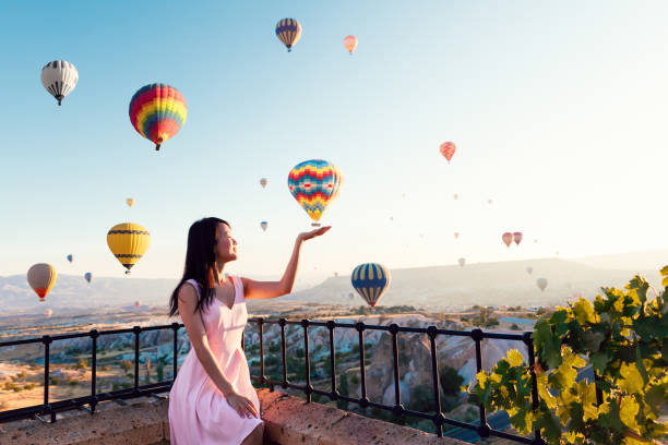 Pretty asian girl open arms watching colorful hot air balloons flying over the valley at Cappadocia, Turkey Woman, Hot Air Balloon, Sunrise - Dawn, Asia, Cappadocia anatolia stock pictures, royalty-free photos & images