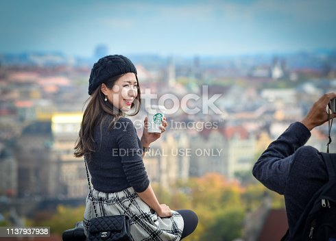 Prague, Czech Republic - October 10, 2017: Pretty Asian girl poses, holds starbucks coffee and looks at the old city of Prague from observation decks near Prague Castle, Prague Czech Republic