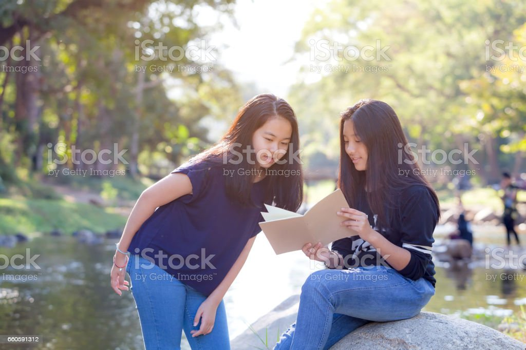 Pretty Asian students reading from notebook royalty-free stock photo