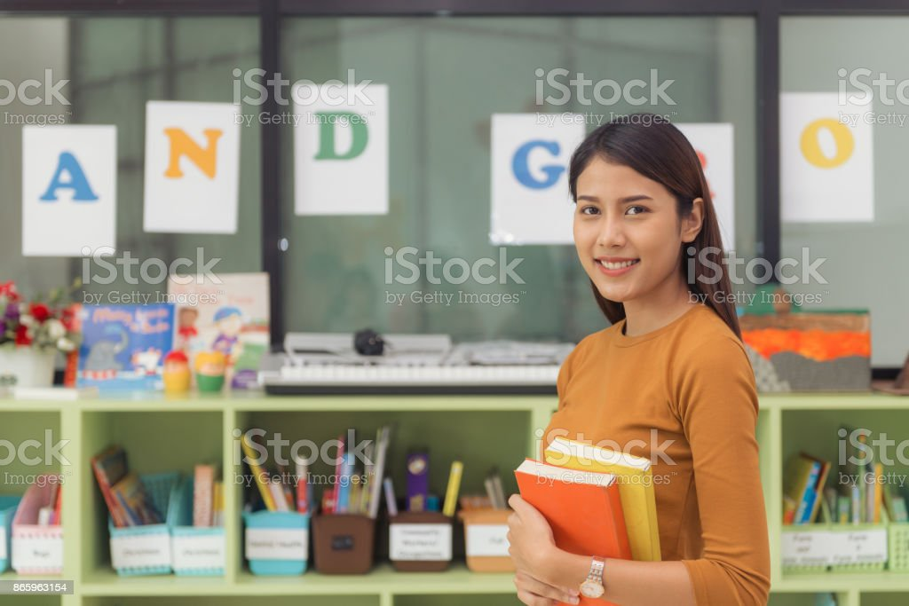 Pretty asian teacher smiling at camera at back of classroom at the elementary school. Vintage effect style pictures. stock photo
