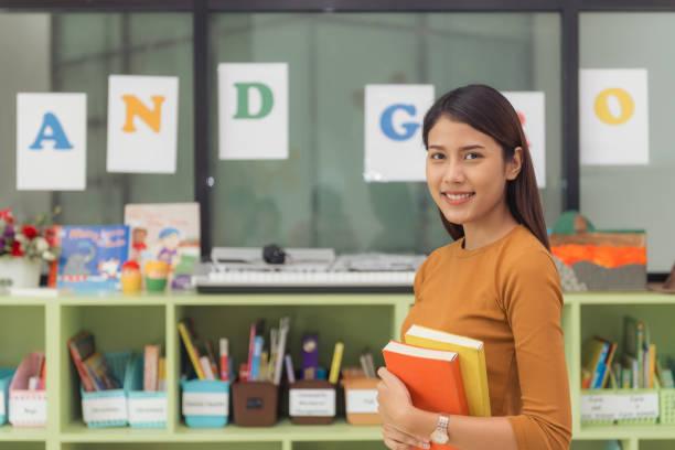 相當亞裔老師笑在小學教室後面的相機。老式的影響風格圖片。圖像檔