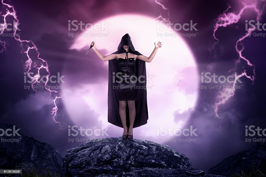 Pretty asian witch woman with cloak holding sharp knife stock photo