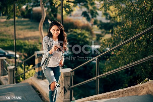 istock Pretty Asian woman climbing the steps and texting. Tourist photo. 1209125380