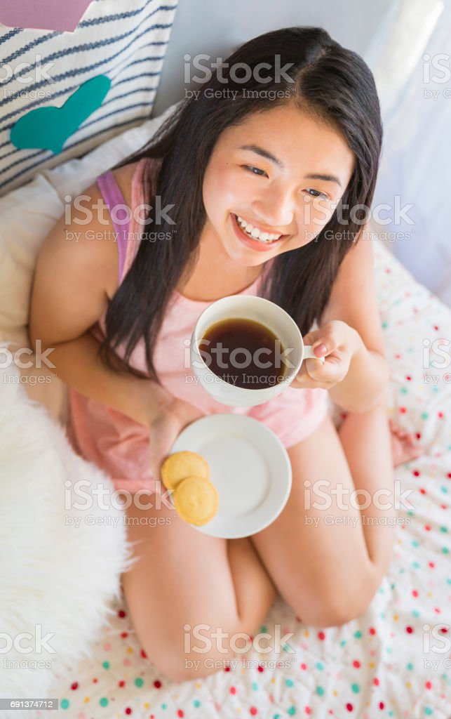 Pretty Asian Young Woman Having Breakfast in Bed stock photo