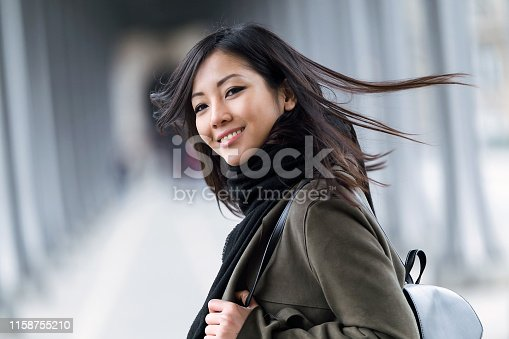 istock Pretty asian young woman smiling and looking at camera in the street. 1158755210