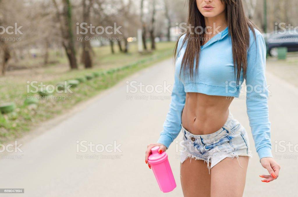 pretty athletic girl in denim shorts skating outdoors royalty-free stock photo