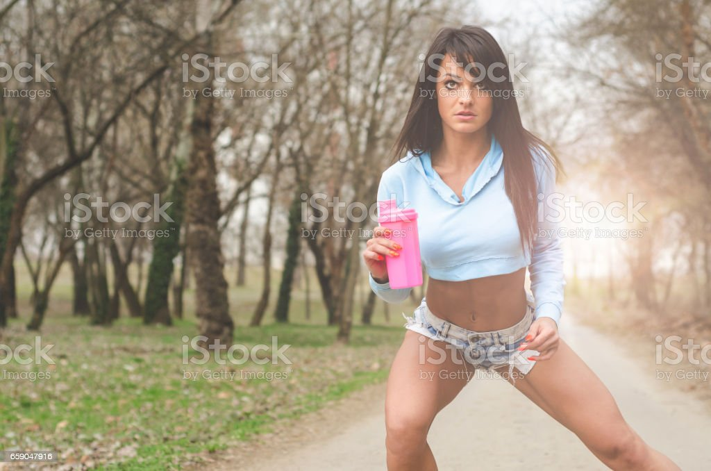 pretty athletic girl in denim shorts skating outdoors royalty-free stock photo