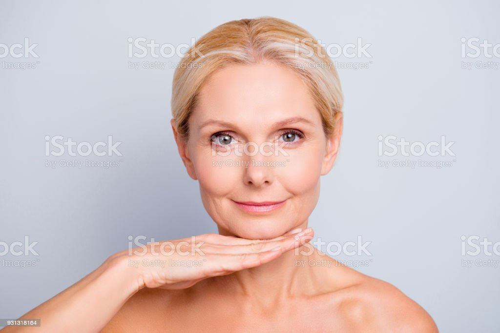 Pretty, attractive, charming,  woman demonstrate, show, present her perfect skin after peeling, lotion, mask, isolated on grey background, holding hand under chin, treatment, therapy concept stock photo